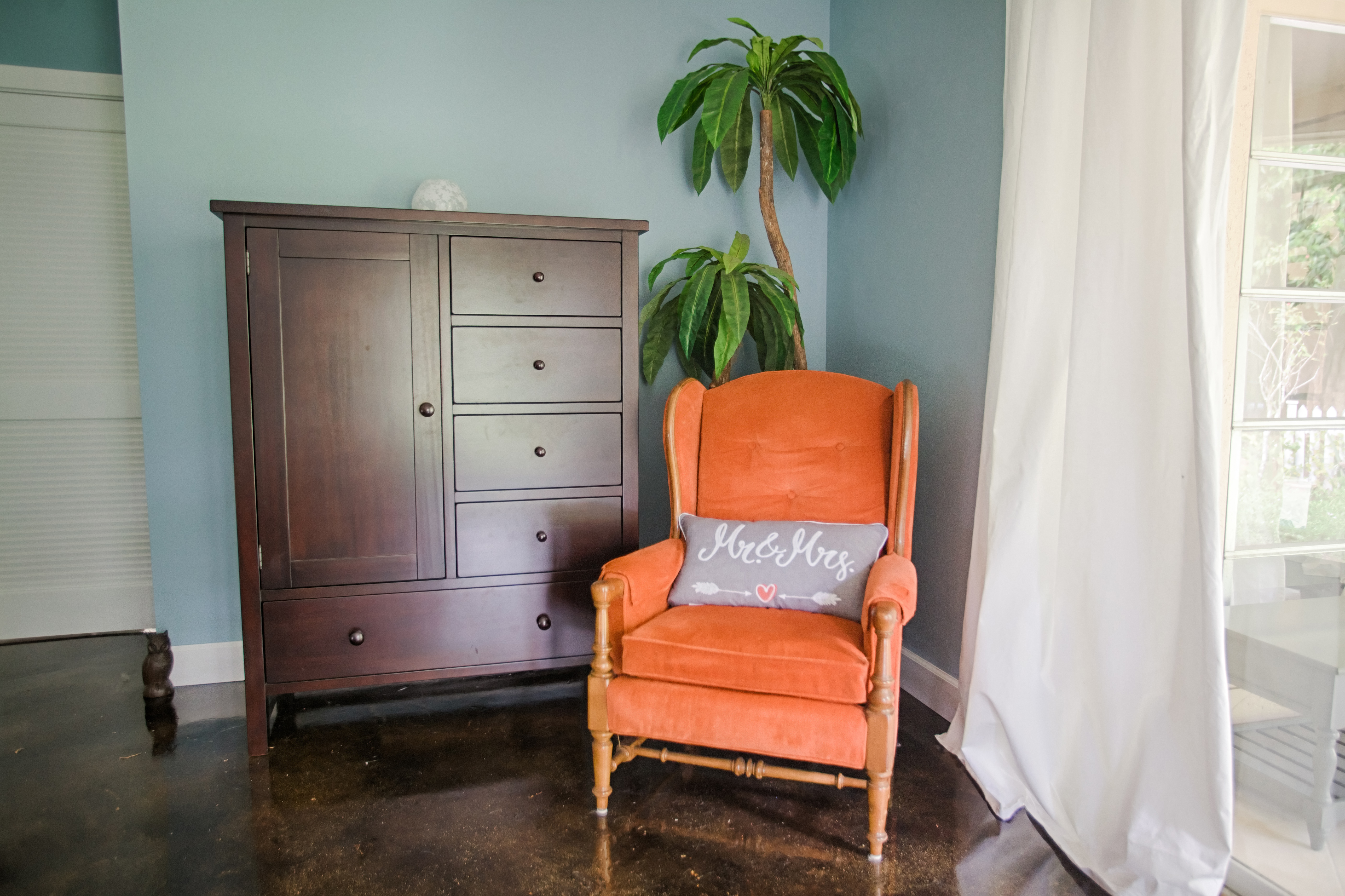 An orange chair - a family heirloom - provides a pop of color in the master bedroom